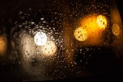 Raindrops and light reflecting on window