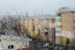 Raindrops på det glass fönstret med byggnader beskådar Royaltyfri Fotografi