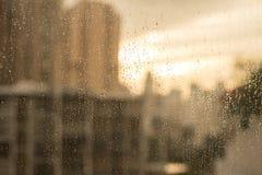 Raindrops på det glass fönstret med suddighetsbyggnader och värme signalen Royaltyfri Fotografi