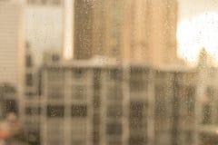 Raindrops på det glass fönstret med suddighetsbyggnader och värme signalen Royaltyfria Foton