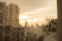Raindrops på det glass fönstret med suddighetsbyggnader och värme signalen Fotografering för Bildbyråer