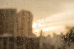Raindrops på det glass fönstret med suddighetsbyggnader och värme signalen Arkivbilder