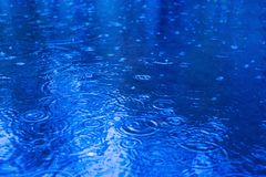 Raindrops on a puddle on a rainy day. stock photos