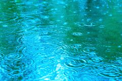 Raindrops on a puddle on a rainy day. Blue tone. stock photo