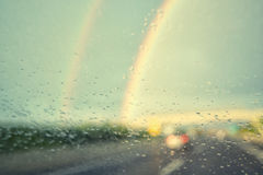 Raindrops and rainbows on car windshield Royalty Free Stock Image