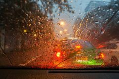 Raindrops with rear car light bokeh at night on car wind shield during storm Royalty Free Stock Image