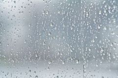Raindrops running down glass pane. Close up of rain drops on a glass pane running down Royalty Free Stock Image