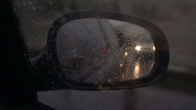 Raindrops on the side mirrors of the car, close-up. Raindrops on the side mirrors of the car while driving in the evening. The mirror reflects the lights of the stock video footage