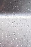 Raindrops on the silver car. Abstract of water dripping on a silver wall after rain fall stock photo