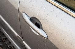 Raindrops on a silver car on the side front door, visible handle. royalty free stock images