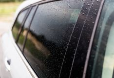 Raindrops on a silver car on the side rear black window of the car. stock photography