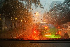 Raindrops and street light bokeh on wind shield Stock Photography