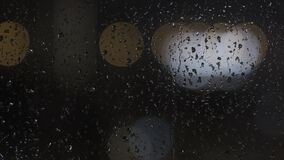Raindrops trickle down the glass, night city lights
