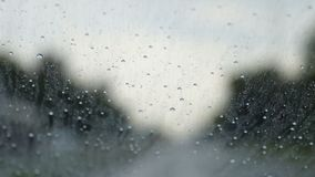 Raindrops trickle down the windshield of moving car on the road stock video footage