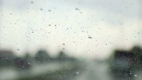 Raindrops trickle down the windshield of moving car. Slow motion stock video
