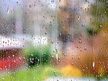 Raindrop trickles against a colorful, yet somewhat spooky  bokeh background. Raindrops trickling down the windowpane with bright-colored bokeh background turning Stock Photos