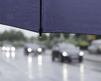 Raindrops On Umbrella. Raindrops on open umbrella seen from below, blurred background with cars driving down the street in the rain Royalty Free Stock Photo