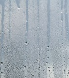 Raindrops and Water Runs on a Glass  Window Pane. A portrait image of a textured background, of raindrops and water runs on a glass window pane.  A neutral dull Stock Photography