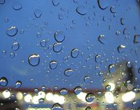 Raindrops on window. Raindrop on a car window with store light in background Stock Image