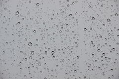 Raindrops on window with black stormy weather outside Stock Photography