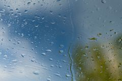 Raindrops on a window a blue sky of a cloud. Raindrops on a window a blue sky of a cloud royalty free stock photography