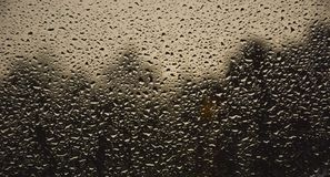 RAINDROPS ON A WINDOW WITH A BLURRED BACKGROUND. A landscape shot of raindrops on a window with blurred trees in the background royalty free stock photography