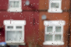 Raindrops on window with English red bricks house in background. Royalty Free Stock Image