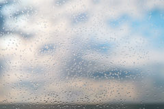 Raindrops on the window. Raindrops on a window glass against blue sky with clouds Stock Photos