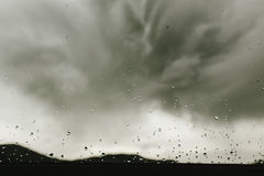 Raindrops on window glass on background of gray clouds, rainy we Royalty Free Stock Photography