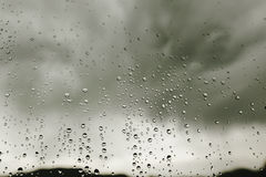 Raindrops on window glass on background of gray clouds, rainy we Royalty Free Stock Images