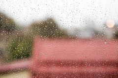 Raindrops on window glass with cloudy sky and city roofs as back royalty free stock photography