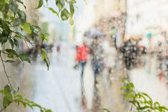 Raindrops on window glass, few unrecognizable people rush home under umbrellas, abstract blurred background. Concept of. Raindrops on window glass, few Stock Photo