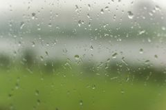 Raindrops on the window glass. Raindrops in focus, the background is beautifully blurred. In the background a blurred field royalty free stock photo