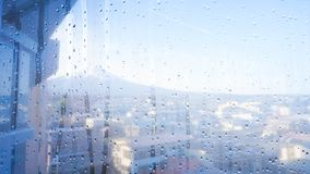 Raindrops on window glass with Fuji mountain. Raindrops on window glass with Japan mountain Fuji view background Stock Photo