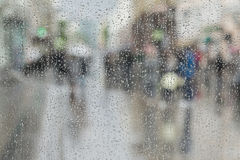 Raindrops on window glass, people walk on road in rainy day, blurred motion abstract background. Concept of shopping Stock Images