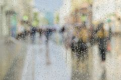 Raindrops on window glass, people walk on road in rainy day, blurred motion abstract background. Concept of shopping Royalty Free Stock Photo