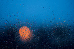 Raindrops on window glass at rainy night Royalty Free Stock Images