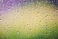 Raindrops on a window. Raindrops on the home window surface against colorful green and yellow background Stock Photos