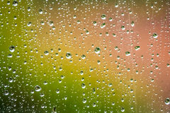 Raindrops on a window. Raindrops on the home window surface against colorful green and yellow background Stock Photo