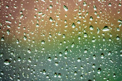 Raindrops on a window. Raindrops on the home window surface against colorful green and yellow background Royalty Free Stock Images