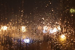 Raindrops on a window late in the evening Stock Images