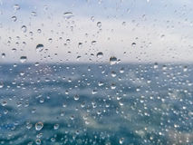 Raindrops on window with ocean water. Close up of raindrops on window with blurred ocean water and sky Stock Images