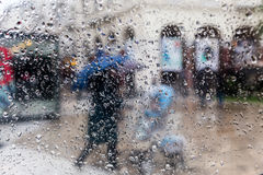 Raindrops on a window pane. Blur people in the rain Royalty Free Stock Image