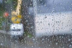 Raindrops on the window pane. A blurred silhouette of special equipment is visible from the window