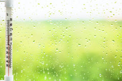 Raindrops on window pane and thermometer Royalty Free Stock Image