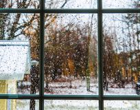 The raindrops are on the window pane. A yellow house is visible and we see in the distance the trees. There is a depth of field effect. Drummondville, Quebec Stock Image