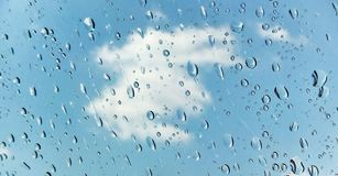 Raindrops in the window. A picture of raindrops in a car window,and a white cloud in the blue sky in a summer day in a greek area,halkidiki Stock Images