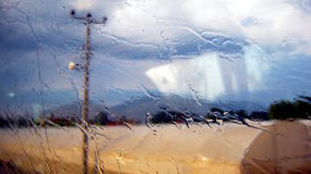 Raindrops on window. Smeared raindrops on side window of coach on the first plane. On the second plane blurred semaphore Stock Photo