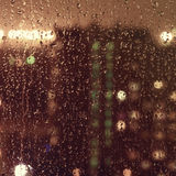 Raindrops on a window surface at night Stock Photography