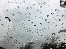 The raindrops on the windscreen or windshield or car glass. View from the inside of the car with a grey sky background. Adjust the. The raindrops on the royalty free stock image